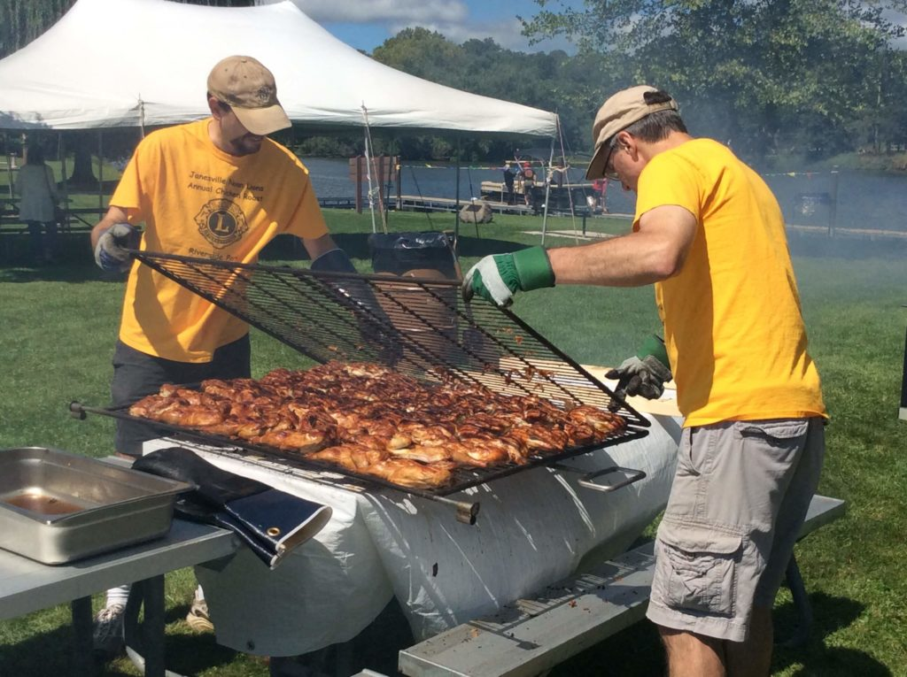 Lions Club members check on hot, grilled chicken on the grill