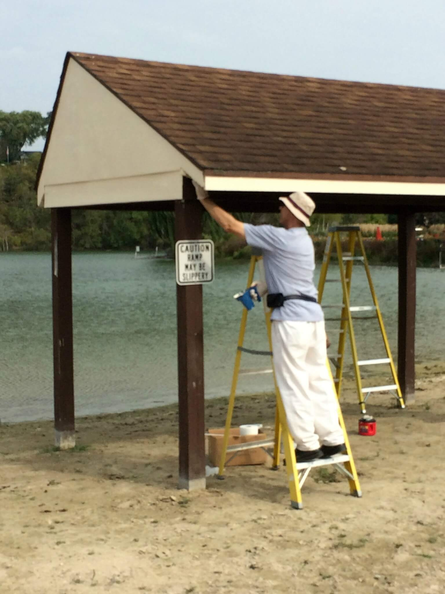 Lion Blaine paints a Lions Beach shelter as part of the Club's Centennial Community Legacy Project.